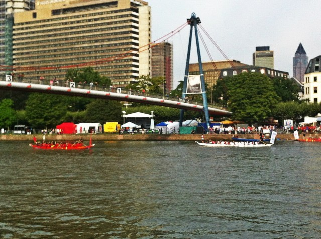 Ett gäng företagsarbetande nissar paddlar vikingabåt längs med Main. Först under bron vinner!